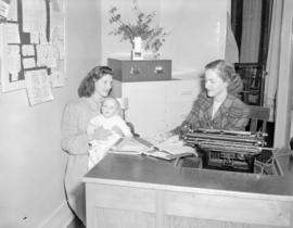 [Woman with a baby talking with a woman at a typewriter]