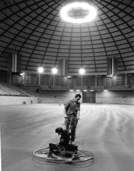 Man with machine preparing the floor of the Agrodome