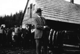 [Board of Trade trip - Mayor L.D. Taylor holding string of fish at] Summit Lake
