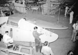[Men and women constructing airplanes at the Boeing aircraft plant on Georgia Street]