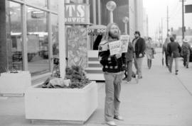 Man sells magazines outside the Vancouver Public Library