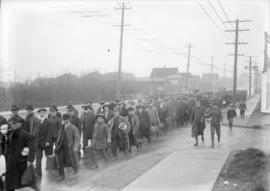 Men marching on the street accompanied by men in uniform