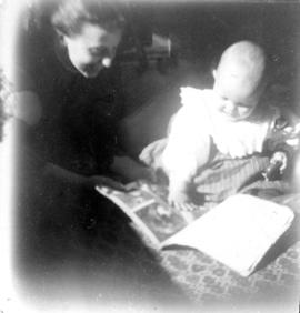 [Winifred Mabel Pierce and Theodore Taylor, aged] 17 or 18 mo[nths, looking at a book]