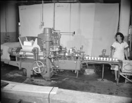 [Woman operating a butter wrapping machine]