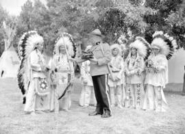 [RCMP officer handing baseball glove and bat to Stoney Indians at the Calgary Stampede Grounds]