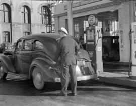 [Harry Howe's service station attendant at the pump filling up a car]