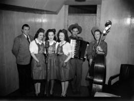 "[Three women in ""Miss Canada"" dresses with some musicians broadcasting on CJOR radio]"