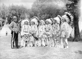 [RCMP officer with group of Stoney Indians at the Calgary Stampede grounds]