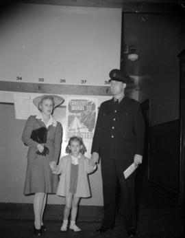 [Policeman and family in front of a war poster]