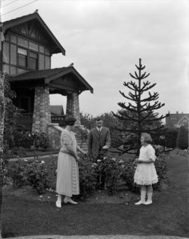 Mr. Johnson [and a woman and girl in garden of house on] Matthews Avenue