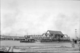 [Baptist Church on barge passing though an open railway bridge on the Fraser River]