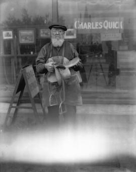 Charles Dad Quick Holding Saddle outside [the] Charles Quick Shoe Repair [1549 Powell Street]