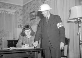 [A.R.P. warden showing papers to a woman seated at a desk]