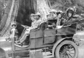 [A group in a car in front of the Hollow Tree at Stanley Park]