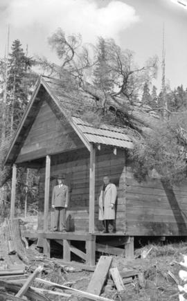 [Premier John Hart and a friend on the porch of the Hollyburn mountain cabin during a visit to re...