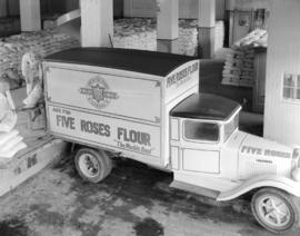 Lake of the Woods truck [being loaded with] Five Roses Flour