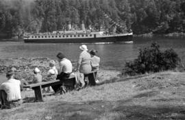 "[Group on shore watching the ""Lady Cynthia"" enter Snug Cove]"