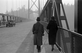 [A man and woman walking across the Lions Gate Bridge]