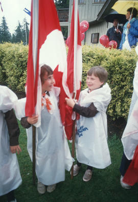 Children holding Canada flags at the Centennial Commission's Canada Day celebration