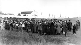 [Crowd surrounding an airplane in a field]