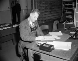 [B.C. Telephone employee with a telephone receiver around his neck at work at a desk during the c...