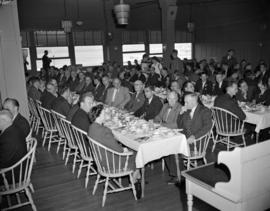 [People seated at dining tables at a food industry luncheon or dinner]