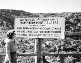 Bea Tait [viewing White Pass and Yukon Route] Inspiration Point, Alaska sign.