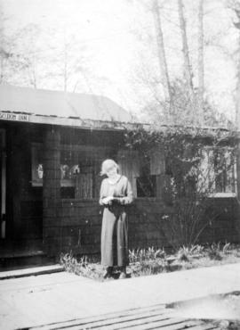[Woman standing in front of the Seldom Inn at Summit Lake]