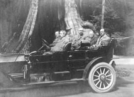 [L.D. Taylor in car with five men in front of hollow tree in Stanley Park]