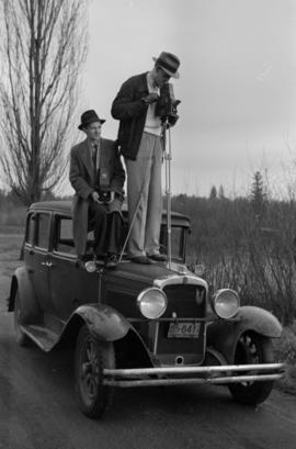 [James Crookall  with camera standing on hood of car]