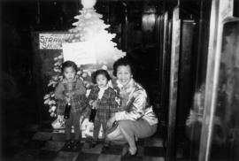 Woman with two children beside cardboard Christmas tree