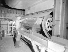 [Man tending peat moss processing machine at] B.C. Peat plant