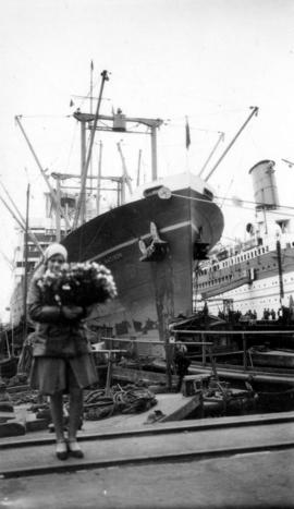 [Girl holding flowers standing on dock in front of the ship [?] Madison]