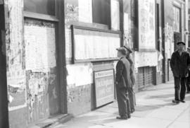 [Men reading posted newspapers in Chinatown]
