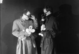 Two men in trench coats holding stuffed animals