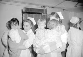 [Nurses carrying children during an air raid drill at St. Paul's Hospital]