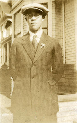 [Young man in suit standing in front of houses]