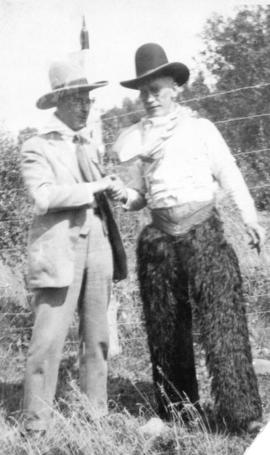 [L.D. Taylor in cowboy hat standing with man dressed in cowboy apparel]