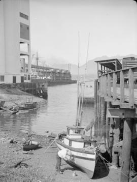 "[Man repairing hull of ""Pavica"" on shore near grain elevator]"