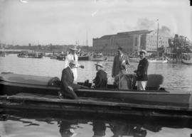 An officer and civillians on a small boat at the dock