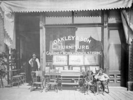 [Isaac Oakley in the doorway of Oakley and Son Furniture, Cabinet Work and Upholstering on Westmi...
