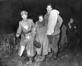 [A shoeless Hungarian refuge is helped to the border by a soldier and customs officer]