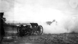 Five soldiers firing a cannon