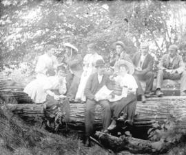 [Men and women seated on log for picnic]