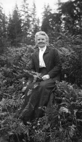 [Portrait of older woman, seated outside among ferns]