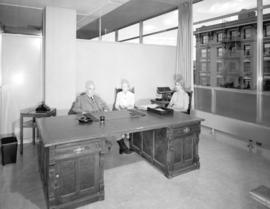 [Major J.S. Matthews, City Archivist, with Mrs. Jean Gibbs and another woman at his desk in the C...