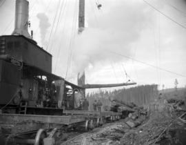 [Logs being loaded off rail cars at the H.R. MacMillan Co. sawmill]