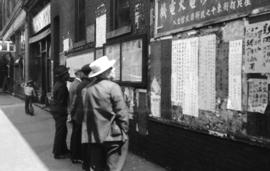 [Men reading Chinese notices and newspapers posted on bulletin boards on Pender Street]