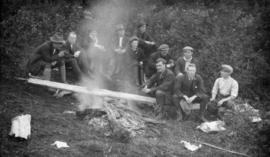 [James Crookall and others sitting around a camp fire]