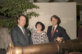 Gordon Campbell and two Bay employees beside cannon at Legacies Program event at The Bay